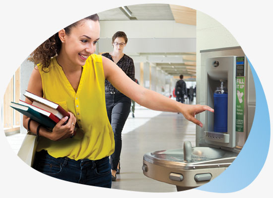 Lady reaching for fresh drinking water from bottle filling station